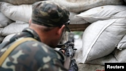 A pro-Russian fighter mans a checkpoint in the eastern Ukrainian city of Donetsk on July 7.