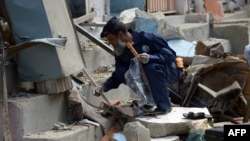 A security official collects evidence at the site of a bomb attack in Karachi, April 24, 2014.