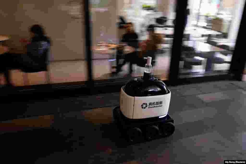 Робот їздить навколо торговельного центру і роздає санітайзери для рук. Шанхай, Китай