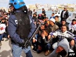 Итальянский полицейский и беженцы из Северной Африки. Остров Лампедуза, юг Италии