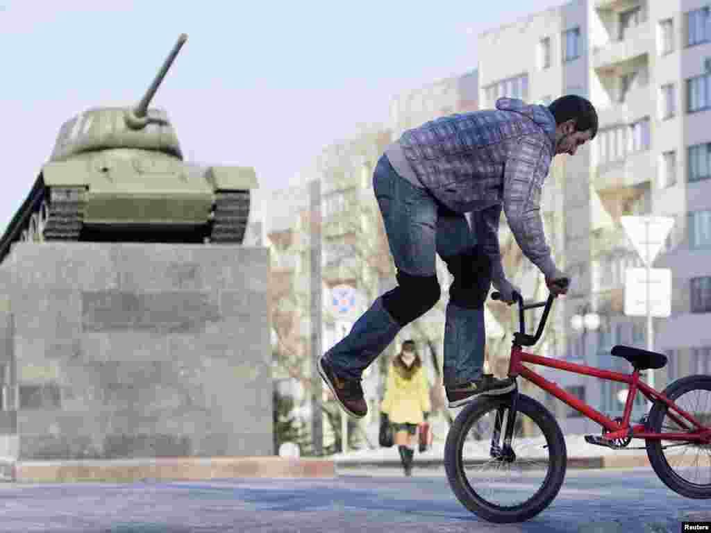 Підліток виконує велосипедні трюки перед пам'ятником на честь Другої світової війни у столиці Білорусі Мінську