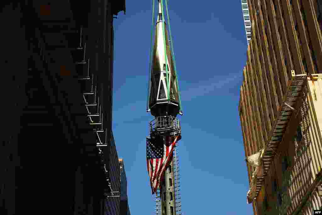 The 408-foot spire is hoisted onto a temporary platform on the top of One World Trade Center in New York. The piece will be attached at a later date.