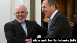 Russian Foreign Minister Sergei Lavrov (right) and Iranian Foreign Minister Mohammad Javad Zarif smile as they enter a hall for talks in Moscow on December 30.