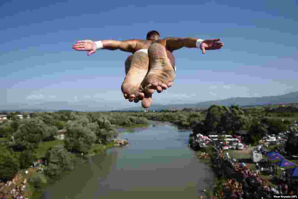 Spectators watch as a competitor takes part in an annual high diving contest near the town of Gjakova in Kosovo. (AP/Visar Kryeziu)