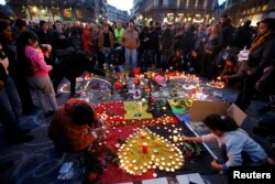 People gather around an impromptu memorial in Brussels to pay tribute to the victims of the bombing attacks.