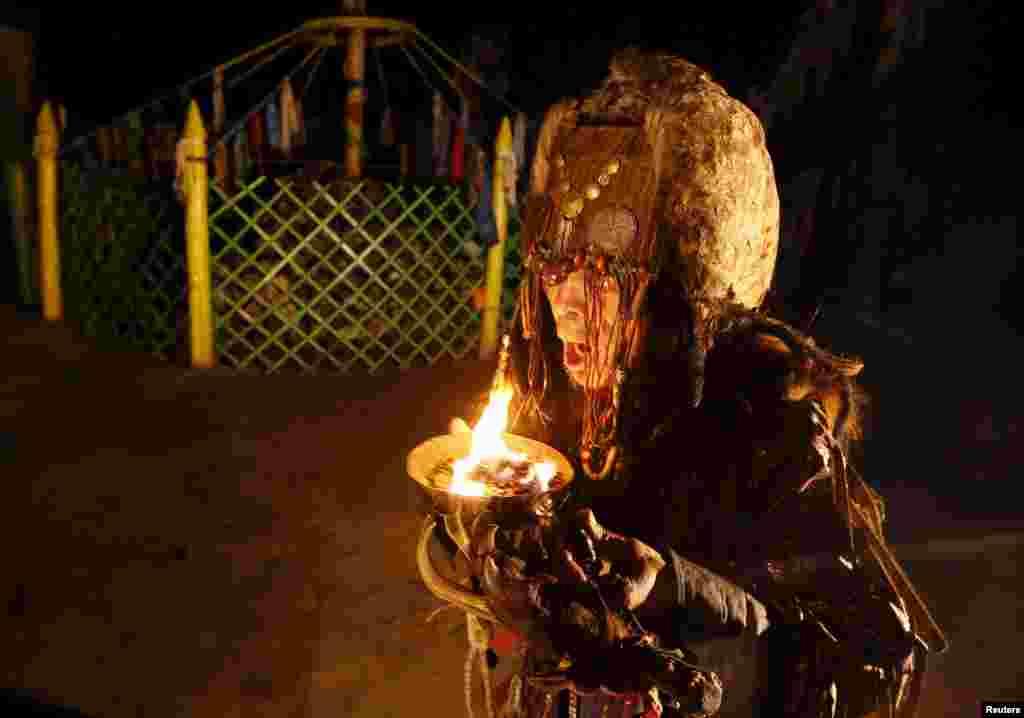 """На фото — шаман из общества """"Адыг Ээрен"""" (""""Медвежий дух"""") пытается войти в транс и связаться с духами умерших через ночной ритуал камлание (священный шаманский ритуал)."""