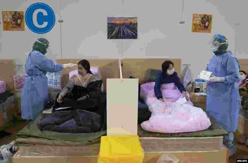 Медицински персонал преглежда пациенти в полевата болница Фангдзън, направена специално за пациенти с коронавирус в китайския град Ухан, който се смята за мястото, от където тръгна заразата. 14 февруари, провинция Хубей.