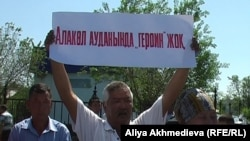 Участник акции протеста в защиту местного предпринимателя держит плакат с надписью, которая в переводе на русский язык означает: «В Алакольском районе героина нет». Ушарал, Алматинская область, 23 мая 2011 года.