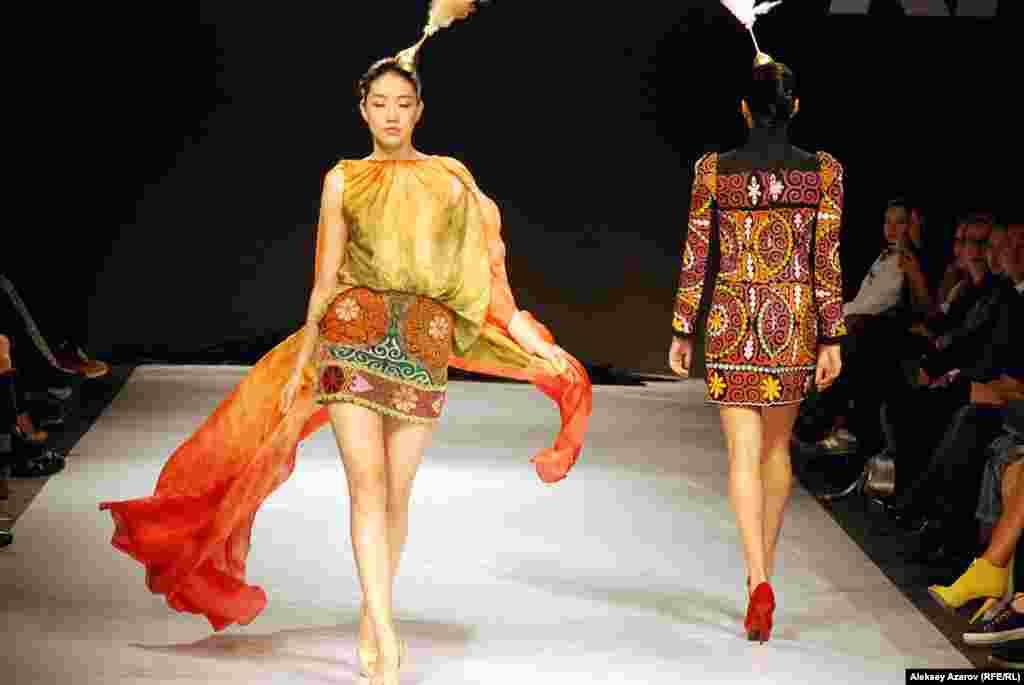 """Ая Бапани (Казахстан) представила, пожалуй, самую яркую и самую роскошную коллекцию первого дня показа. Модели дефилировали по подиуму под запись этнической музыки в исполнении скрипачки Жамили Серкебаевой. Как сказала музыкантрепортеру Азаттыка, для нее это - """"приятный сюрприз""""."""