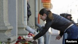 A woman lays flowers near the entrance to the Oktyabrskaya metro station in Minsk, where 15 people were killed in an explosion on April 11.