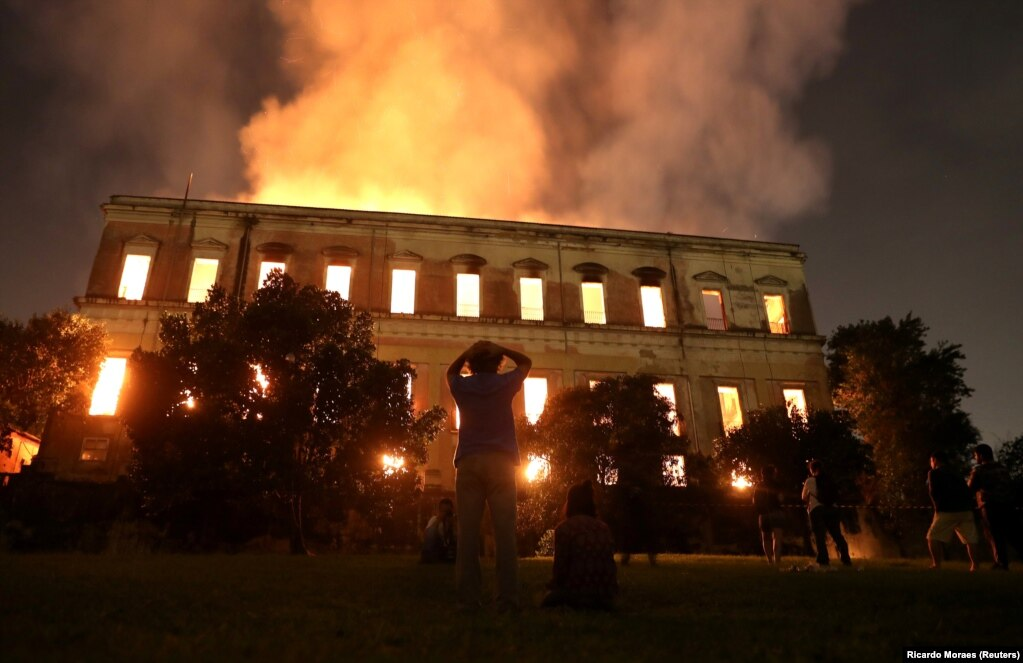 People watch as a fire burns at the National Museum of Brazil in Rio de Janeiro. Authorities fear the destruction of more than 20 million items. The cause of the fire is not yet known.(Reuters/Ricardo Moraes)