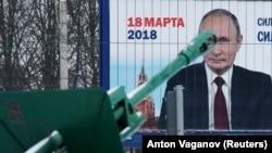 Историческая пушка рядом с рекламным щитом, на котором изображен портрет президента России Владимира Путина и указана дата президентских выборов. Петербург, 19 февраля 2018 года.