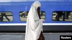 Женщина к никабе идет по перрону одного из парижских железнодорожных вокзалов. 11 апреля 2011 года.