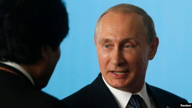 Russian President Vladimir Putin talks with Bolivia's President Evo Morales as they attend the official photo session during the sixth BRICS summit and the Union of South American Nations (UNASUR), in Brasilia July 16, 2014.
