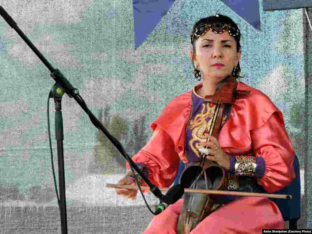 A Kazakh musician performs traditional nomadic music, playing the Qobyz, an ancient musical instrument