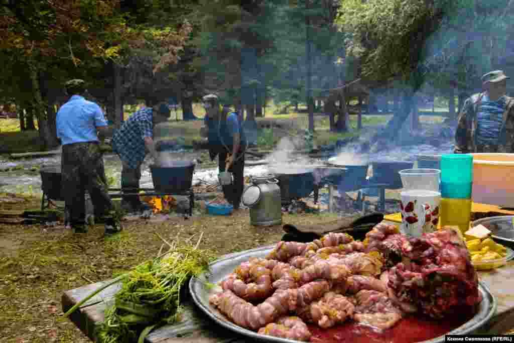 На берегу горной речушки всем селом готовят праздничное застолье. У казанов – только мужчины. Как поясняют местные, женщины подготавливают, а мужчины готовят. В меню много национальных блюд, обязательно с бараниной. В их числе дергем - желудок барана, разрезанный лентой и сплетенный с полоской жира