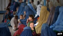 Afghan refugee families wait to be registered at the United Nations High Commissioner for Refugees (UNHCR) repatriation center on the outskirts of Peshawar, April 27, 2017