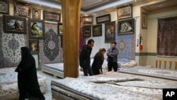 Costumers inspect a hand-woven carpet at the grand bazaar in Kashan
