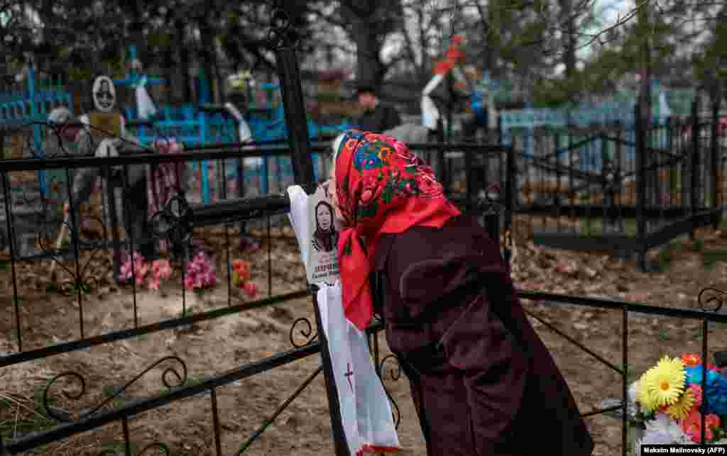 A woman kisses a picture of a loved one in a cemetery in the village of Orevichi, inside the exclusion zone around the Chernobyl nuclear reactor, some 390 kilometers from Minsk, during Radunitsa, the Russian Orthodox commemoration of the departed. (AFP/ Maksim Malinovsky)