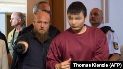 Hussein K (right) enters the courtroom at the regional court in Freiburg on September 5.