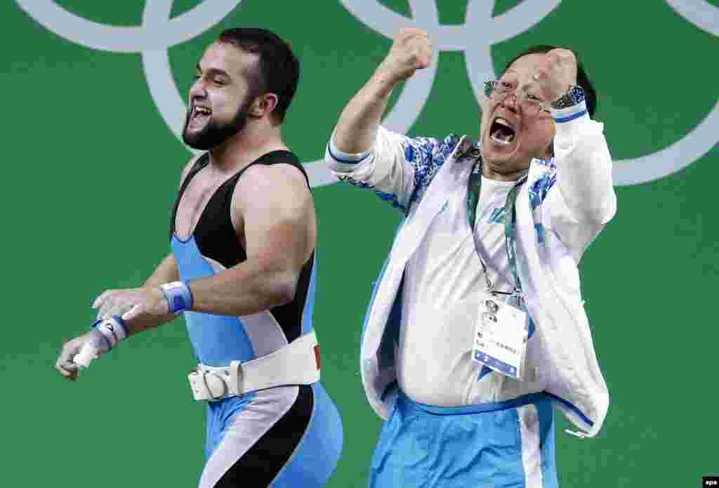 Nijat Rahimov (L) of Kazakhstan celebrates with a member of the coaching staff after setting a new world record and winning the gold medal in the men's weightlifting 77-kilogram category.