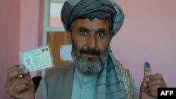 Мужчина держит в руках удостоверение личности гражданина Афганистана.