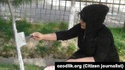 Воспитательница детского сада №450 в Учтепинском районе города Ташкента занимается побелкой деревьев.