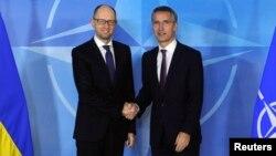 Генэральны сакратар НАТО Енс Столтэнбэрг (справа) паціскае руку прэм'ер-міністру Ўкраіны Арсенію Яцанюку. Брусэль, 15 сьнежня.