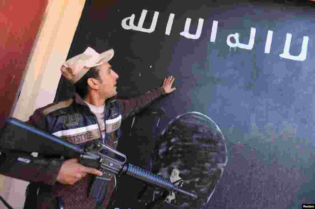 An Iraqi soldier looks at a wall painted in the colors of the black flag commonly used by Islamic State militants, in the village of Argub, Iraq. (Reuters/Ari Jalal)