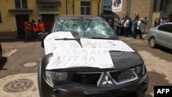 "A damaged car covered by posters reading ""Dadayev is a victim of outrage!"" outside the office of the Committee Against Torture in Grozny after it was ransacked on June 3, 2015."