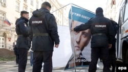 Российская полиция демонтирует постер в поддержку оппозиционного политика и блогера Алексея Навального. Москва, 24 апреля 2014 года