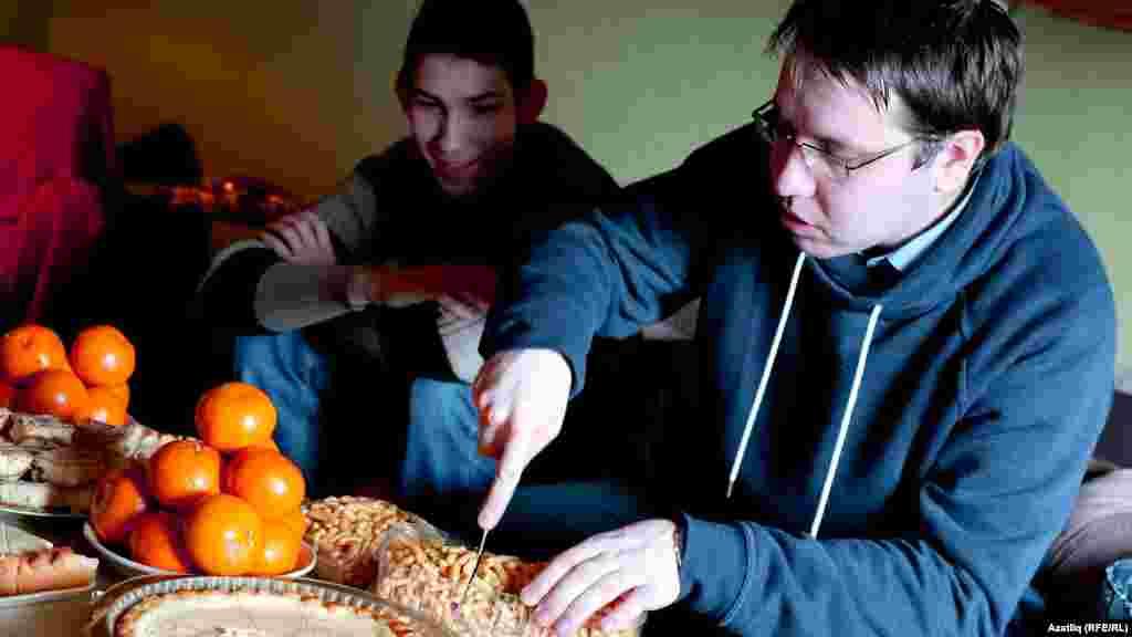 Журналист-мөгаллим Рашат Якупов бәйрәм табыны өчен чәк-чәк кисә, янында укучысы