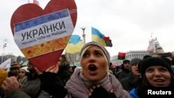"""Участница демонстрации за евроинтеграцию Украины держит плакат с надписью """"Украинки ждут тебя на Майдане""""."""