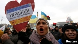 """Тәуелсіздік алаңындағы үкіметке наразылық шеруінде """"Украина әйелдері сіздерді алаңда күтеді"""" деген жазу ұстап тұрған әйел адам. Киев, 15 желтоқсан 2013 жыл."""
