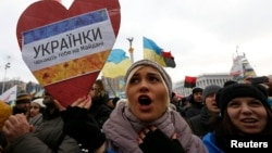 "A woman holds a sign saying ""Ukranian ladies are waiting for you on Maidan"" as she takes part in a pro-EU integration rally in Independence Square."