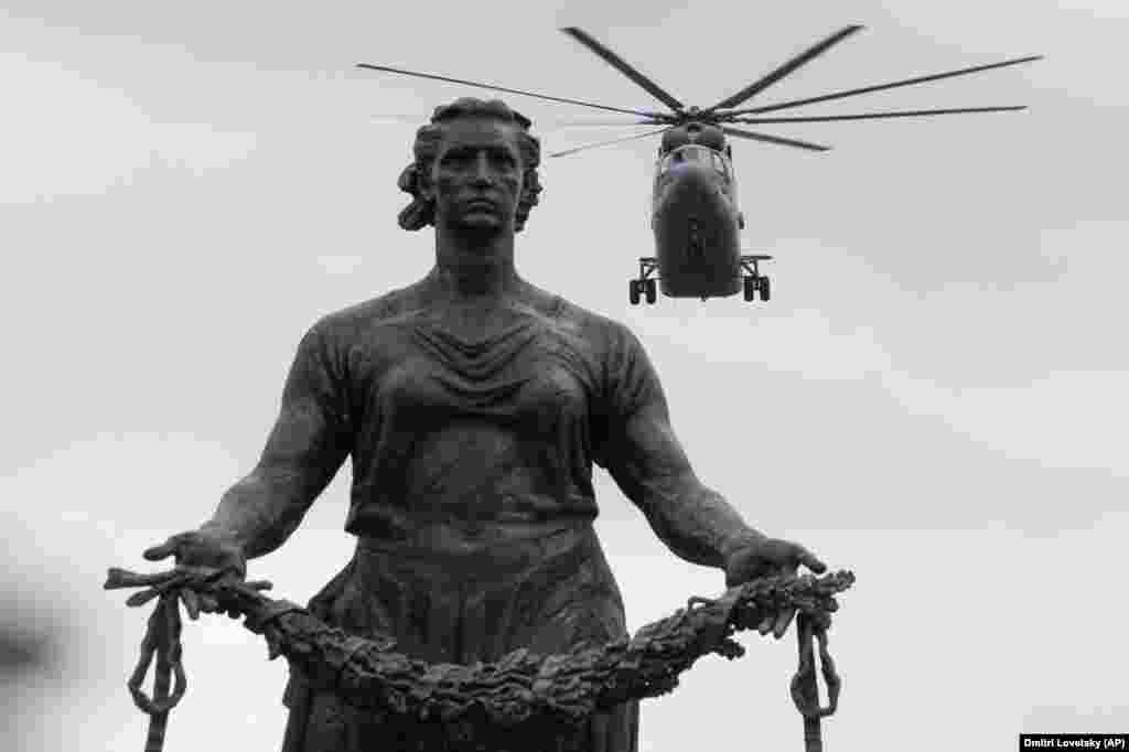 A military helicopter flies over a statue of the Mother Motherland at the Piskaryovskoye Memorial Cemetery in St. Petersburg during a rehearsal for the 2020 Victory Day parade. The monument pays tribute to the more than half a million Leningrad siege victims who were killed during World War II. The military parade to mark the 75th anniversary of the victory over Nazi Germany on May 9 is postponed due to the coronavirus outbreak, leaving only a flyby.