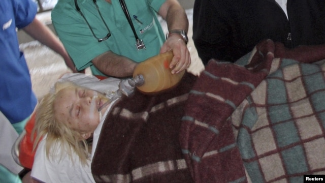 Ukrainian medical staff assist Oksana Makar, the victim of a vicious attack in the southern town of Mykolayiv, as she is brought for treatment to a hospital in Donetsk. She died of her injuries nearly three weeks later.