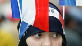 "A Muslim girl displays two French flags and a headband that reads ""Fraternity"" in Paris (file photo)"