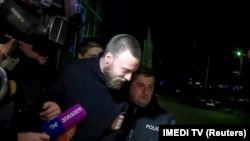 Jack Shepherd is escorted by police in Tbilisi on January 23.