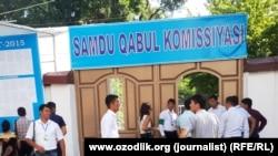 """Студенты перед зданием вуза в Самарканде. Надпись на латинице означает - """"приемная комиссия""""."""