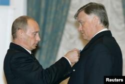 РТЖ басшысы Владимир Якунинді (оң жақта) Ресей президенті Владимир Путин медальмен марапаттап жатыр.