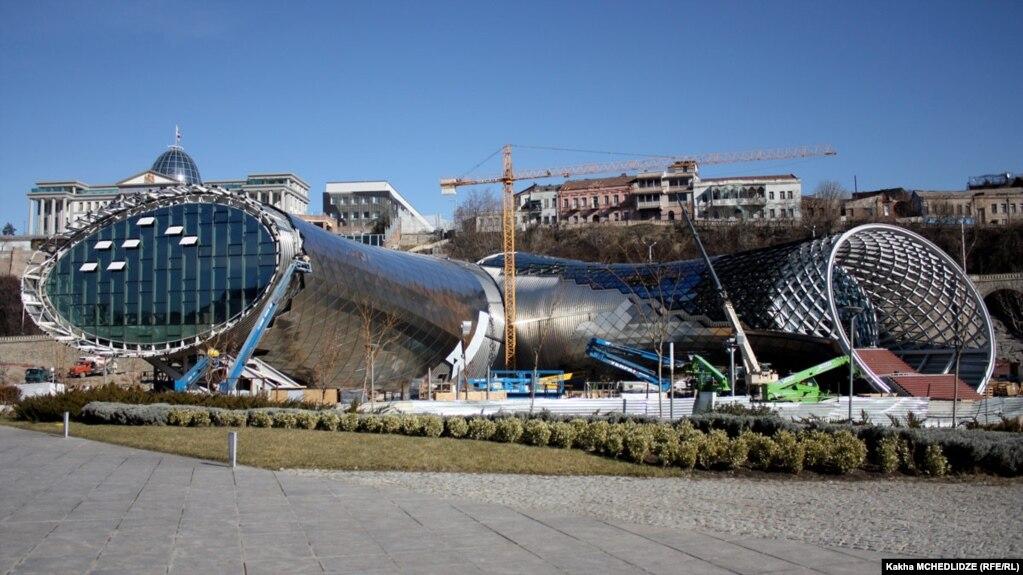Огромная конструкция из стекла и металла в виде двух стилизованных гигантских кувшинов расположилась в старом Тбилиси, в парке Рике. Впрочем, если не знать замысел автора – итальянского архитектора Массимилиано Фуксаса, – то ассоциация с кувшинами может и не прийти в голову. Тбилисцы называют это строение просто «трубами»