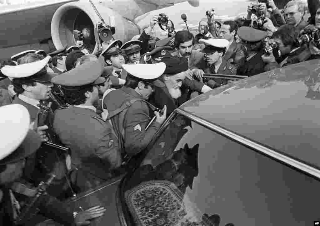 Khomeini has a heavy escort as he tries to leave the airport for his ride through Tehran to Behesht-e Zahra cemetery.