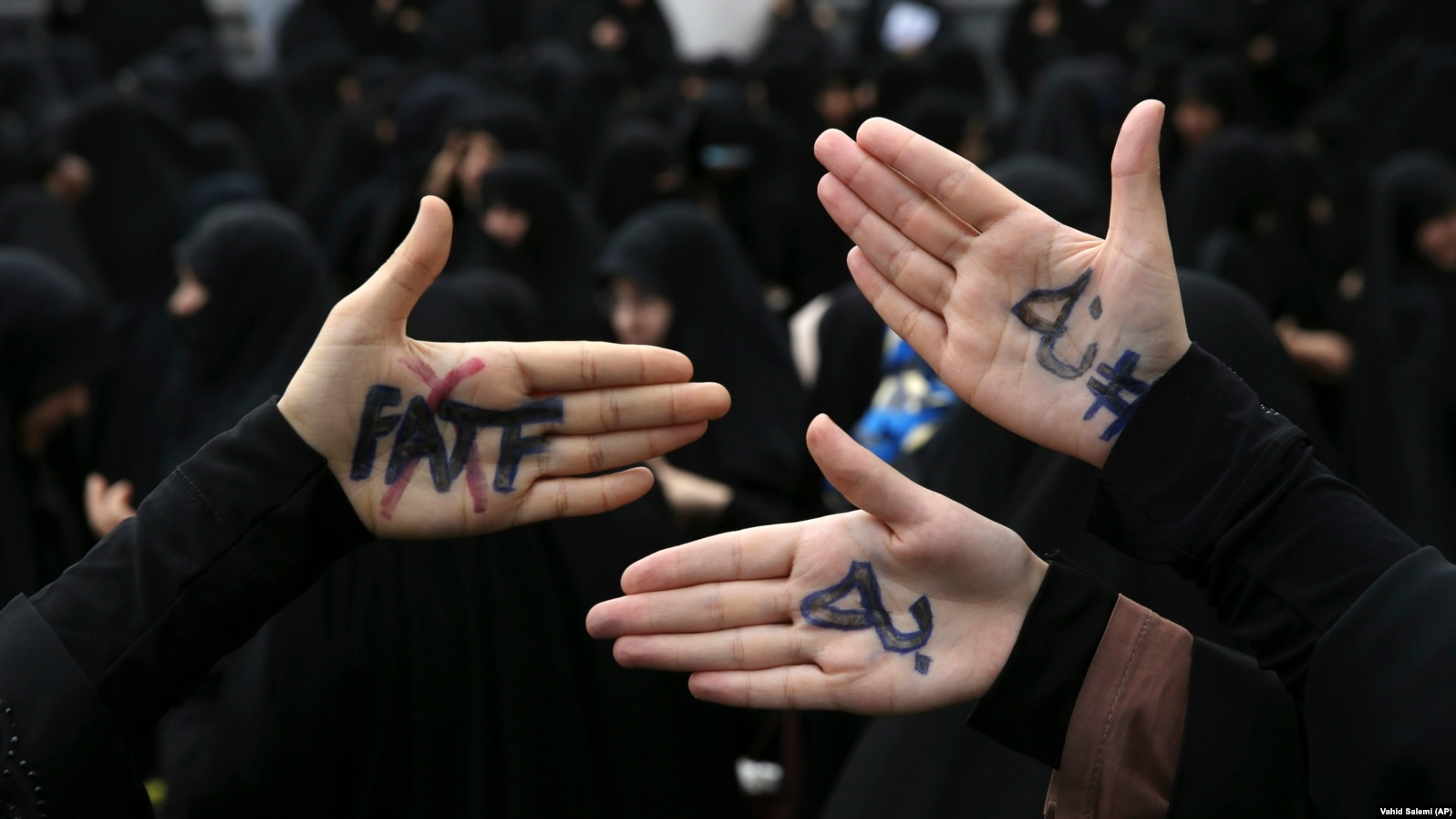 """Hard-line Iranian protesters show their hands with writing in Persian that reads, """"No to FATF,"""" to protest the passage of a bill which joins Iran to the """"Combating the Financing of Terrorism,"""" or CFT, outside the parliament, in Tehran, Iran,"""