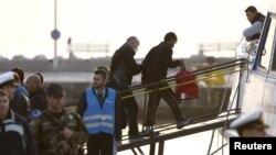 """""""Frontex"""" agentliginiň işgäri migrantlary Türkiýäniň baýdagyny göterýän gämä mündürýär, Gresiýanyň Lesbos adasy, 4-nji aprel, 2016"""