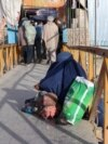 A woman and child beg on a bridge in Ghazni.