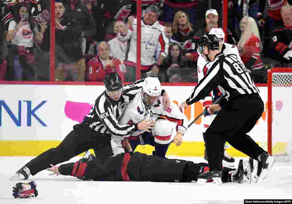Linesman Scott Cherrey pulls Alex Ovechkin of the Washington Capitals off of Andrei Svechnikov of the Carolina Hurricanes during the first period in game three of the Eastern Conference first round during the 2019 NHL Stanley Cup Playoffs in Raleigh, North Carolina. Svechnikov was knocked out and entered the concussion protocol following the fight. Svechnikov needed to be helped off the ice by his teammates following the brawl. (AFP/Getty Images/Grant Halverson)