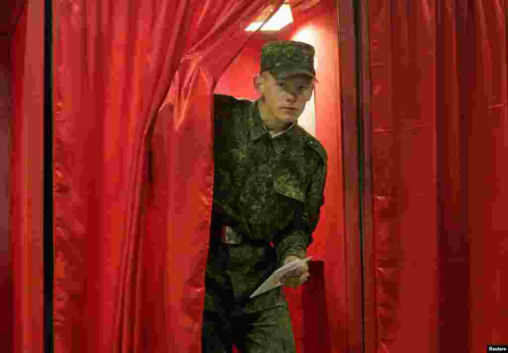 A soldier leaves a voting booth in Minsk.