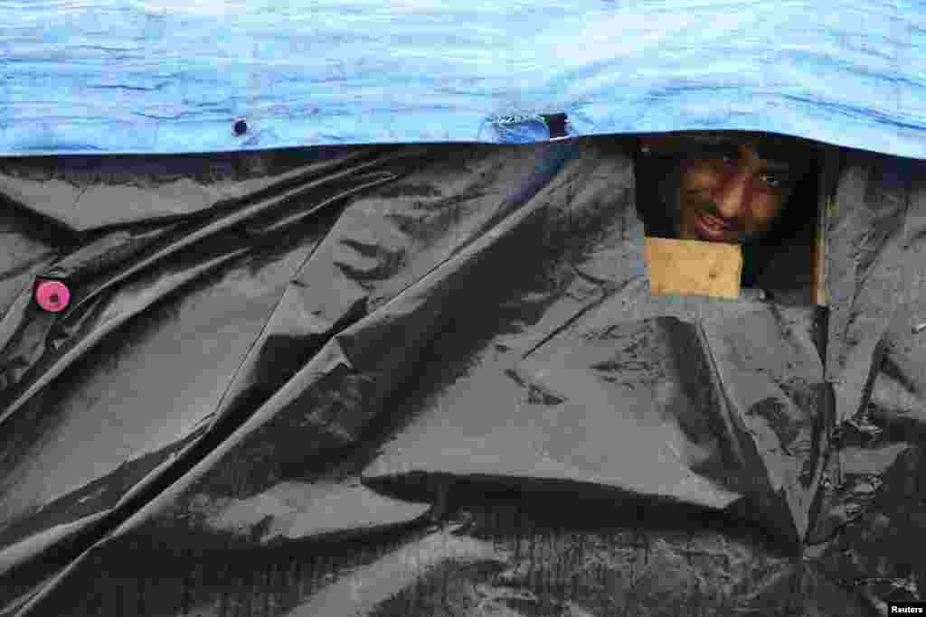 An Afghan migrant looks out the window of his makeshift shelter at the harbour in Calais, France. (Reuters/Pascal Rossignol)