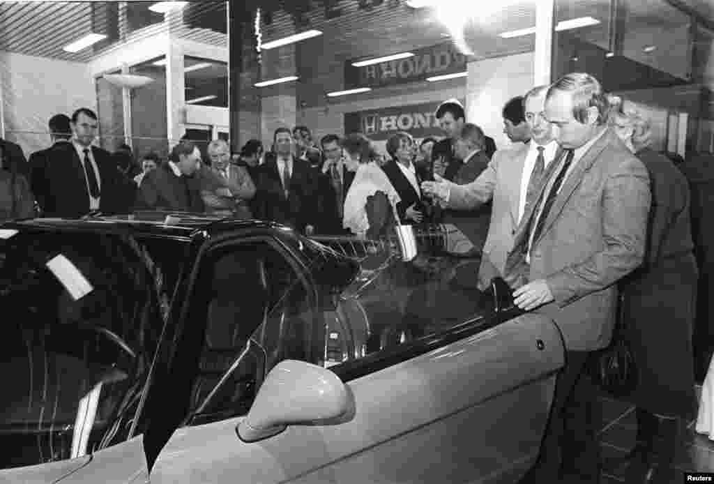 Putin (front right) looks at a Honda car during a ceremony in St. Petersburg on April 29, 1993.
